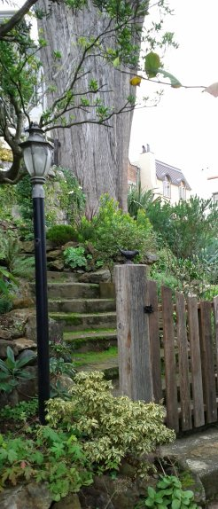 Fun little garden details along the way, like the metal bird on the gatepost under a metal lamp post.