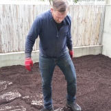 Tony stomping the stepping stones back into position in the new soil, to have an easy path to the gate.
