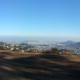 A panoramic shot with downtown to the north (left) and San Bruno Mountain to the south.